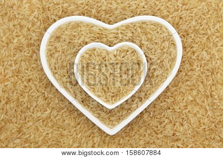 Long grain brown rice in heart shaped porcelain dishes forming an abstract background.
