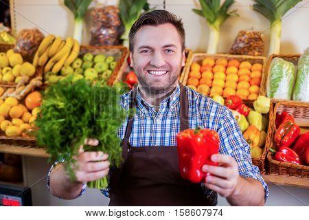 Seller in apron showing fresh vegetables