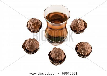 Glass with cognac and chocolate isolated on white background