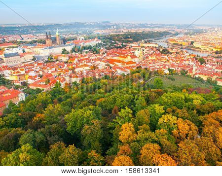 Aerial view of Prague cityscape with Prague Castle, red roofs of Lesser Town, Vltava river, and trees on Petrin Hill on sunny day. Capital city of Czech Republic, Europe
