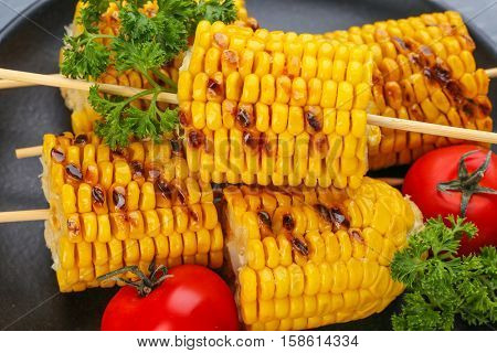 Black plate with grilled corncobs, tomatoes and parsley, closeup