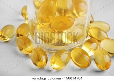 Glass bottle with cod liver capsules on white background