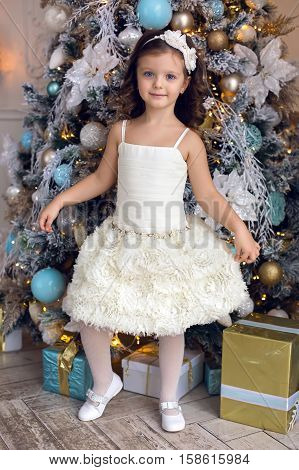 little girl three years old in a white dress smiling at the decorated Christmas tree in room