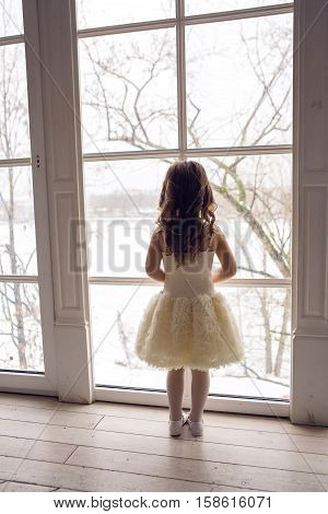 little girl three years old in a white dress and with long hair looking out the window