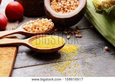 Composition of corn seeds and groats on wooden table