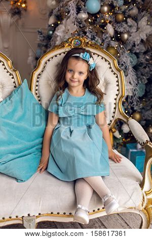 cheerful little girl in a blue dress sitting on chair