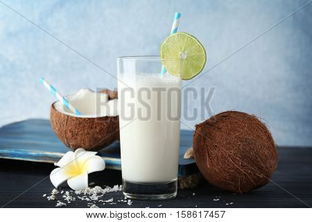 Tasty cocktail with coconut and plumeria on table