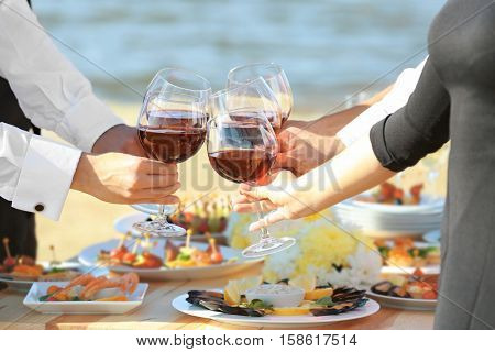 People clinking glasses at buffet catering party outdoors, close up