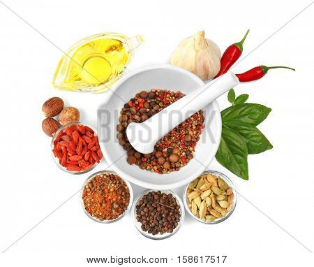 Composition with different spices and mortar on white background