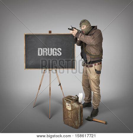 Drugs text on blackboard with terrorist holding machine gun