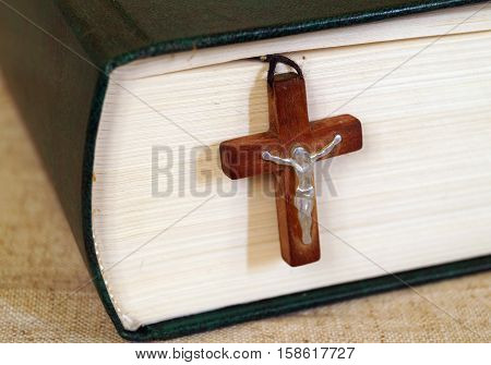 Holy Bible and a wooden cross with Jesus laid between the pages