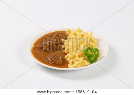 plate of fresh beef goulash with cooked rigatoni pasta