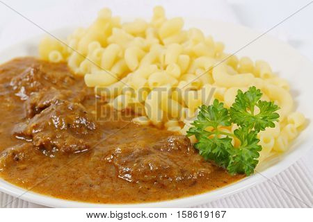 plate of fresh beef goulash with cooked rigatoni pasta - close up