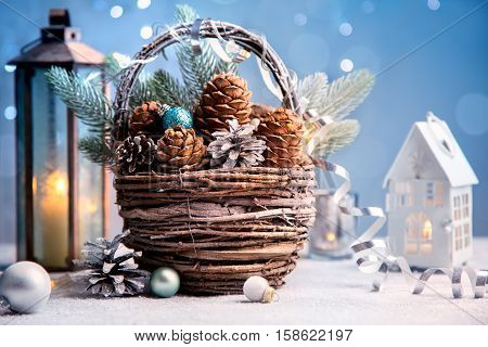 Christmas holiday background. Decorations for Christmas and New Year. Old basket with cones, christmas balls and christmas lanterns.