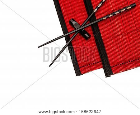 Asian chinese japanese chopsticks on red bamboo mat. Table place setting