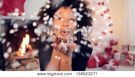 Young woman blowing confetti off her hands