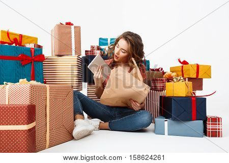 Young beautiful curly girl sitting on floor among gift boxes opening presents Isolated Copy space