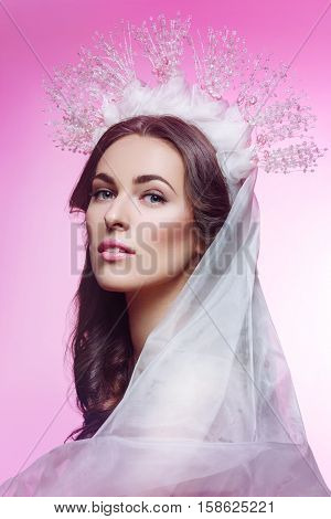 Beautiful young brunette woman in crystal crown and white veil on pink background. Romantic beauty look. Copy space.