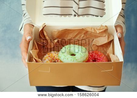 Woman holding carton box with tasty donuts, close up view