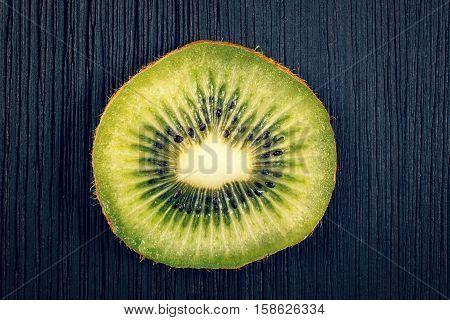 close up of scliced kiwi fruit on black