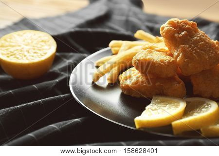 Tasty chicken nuggets with fries and lemon on plate