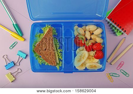 Tasty sandwich and fruits in lunchbox and stationery on pink background