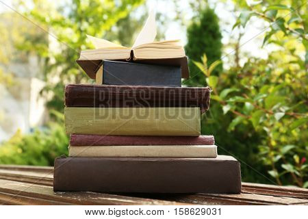 Pile of books on bench in a park
