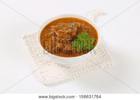 bowl of fresh beef goulash on white table mat