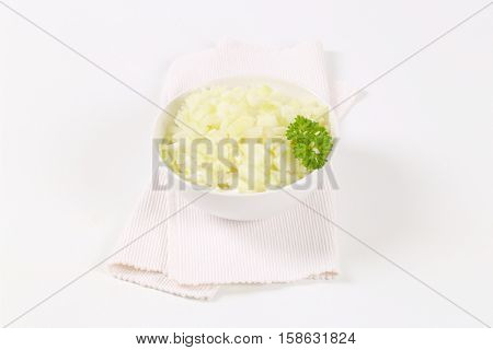 bowl of chopped raw onion on white place mat