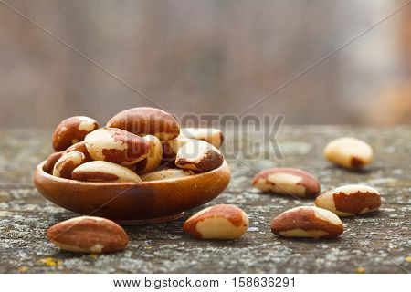 Brazil nuts (Bertholletia excelsa) on rustic wooden table. Healthy food.