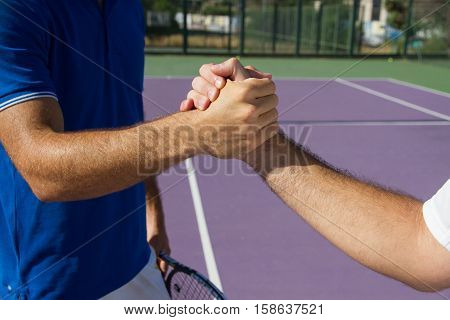 Two men, professional tennis players shake hands before and after the tennis match. In the photo it looks like shaking hands greeting each other closely.