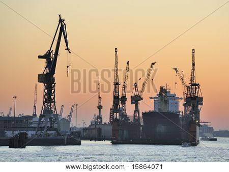 Ship in dry-dock and cranes at sunset
