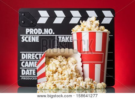 Popcorn boxes with clapper board on a red background