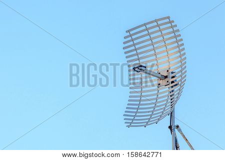 Microwave antenna dish on clear blue sky background.