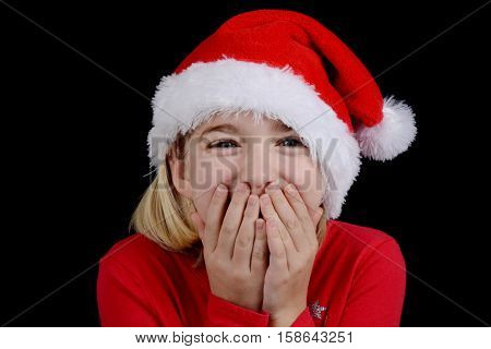 little girl with santa hat and hands over mouth excitement concept