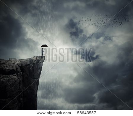 Man with an umbrella stand on the edge of the cliff calling the rain. Mysterious place above the clouds.