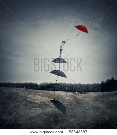 Young boy stand on a stack of umbrellas arranged as a ladder to the sky trying to catch a different red umbrella. The pursuit of happiness and success concept.