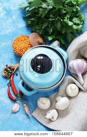Blue cooking pot and ingredients for soup or stew on rustic background