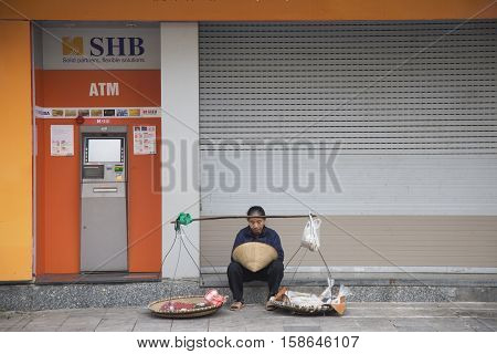 Hanoi, Vietnam - Nov 26, 2016: Vietnamese vendor sitting in front of SHB commercial bank branch on an old quarter street. Vietnam is a developing economy oriented by the state run by Communist Party.