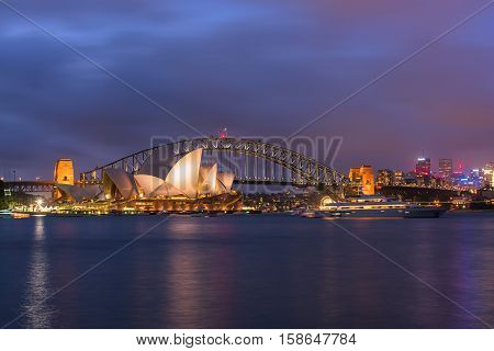 View of  Sydney Opera House And Harbour Bridge at night from Mrs macqurie's Chair.NOV 28,2016 The Sydney Opera House is a famous arts center. It was designed by Danish architect Jorn Utzon, finally opening in 1973.