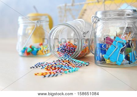 Paperclips and other tools in glass jars