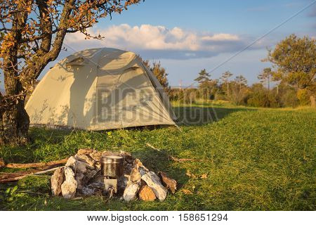 Camp tent stands in the meadow near bonfire site with pot on it at beautiful dawn woodland landscape background under blue cloudy sky.