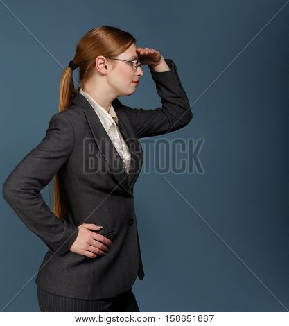 Beautiful stylish young woman with long blonde hair in a ponytail hairstyle in dark grey business suit white chemise and glasses stands with looking far away gesture on blue background.