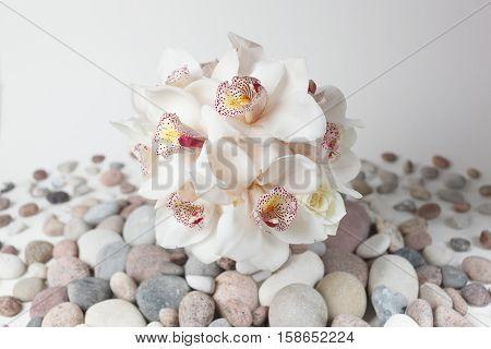Cymbidium orchid wedding bouquet on the stones