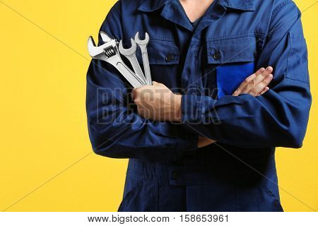 Mechanic with crossed arms and wrench standing on yellow background
