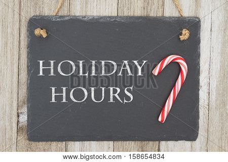 Old fashion Christmas store message A retro chalkboard with a candy cane hanging on weathered wood background with text Holiday Hours