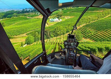 Helicopter cockpit flies in grapevine of Constantia Valley, Cape Town in South Africa, with pilot arm and control board inside the cabin.