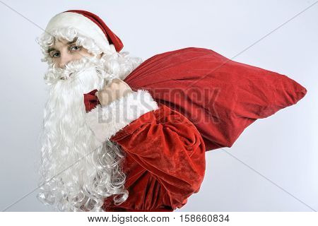 Jolly Santa Claus with a bag of gifts over his shoulder