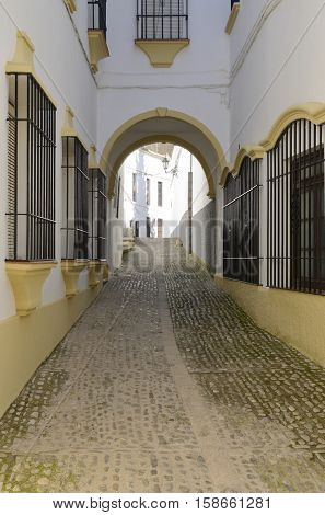 Paving stone way in white alley with a touch of yellow in Ronda Andalusia Spain