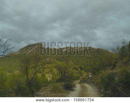 montaña con vegetación y nubes de tormenta